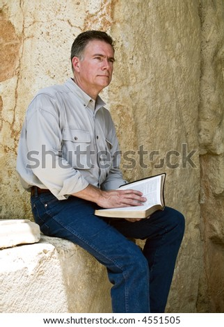 A man with a reflective expression on his face, sitting with what appears to be a bible in his hands. - stock photo