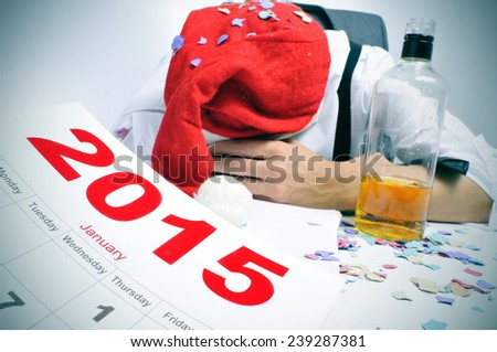 a man with a santa hat and covered with confetti sleeping in his desk after a new years party - stock photo