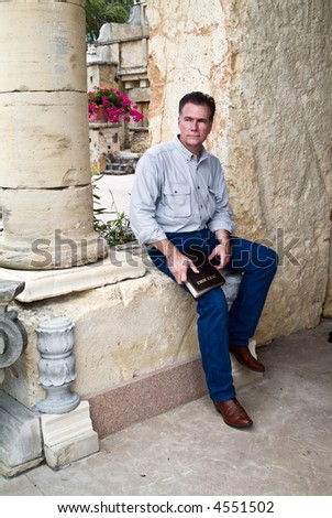 A man with a serious expression on his face, sitting with a bible in his hands. - stock photo