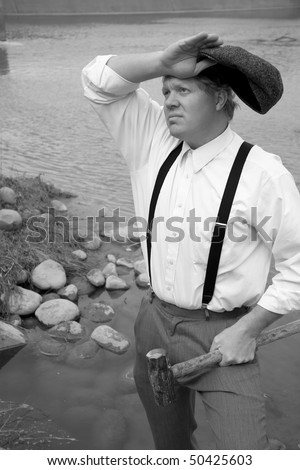 A man with a sledge hammer wiping his brow - stock photo