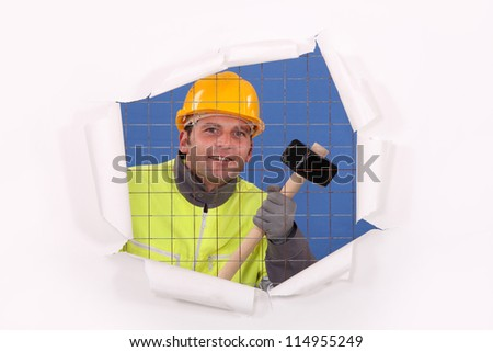 A man with a sledgehammer behind a wire netting. - stock photo