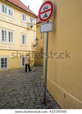 a man with a small dog walks among houses - stock photo