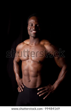 A man with a smile on his face showing off his muscles.
