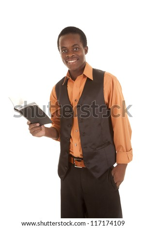 A man with a smile on his face with his hand in his pocket while he is holding on to a book - stock photo