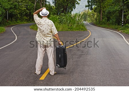 a man with a suitcase is on a fork in the road - stock photo