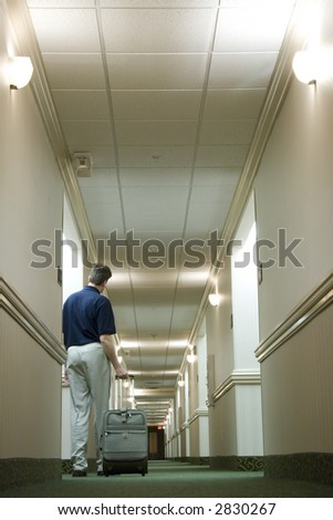 A man with a suitcase is walking down a hotel hallway - stock photo