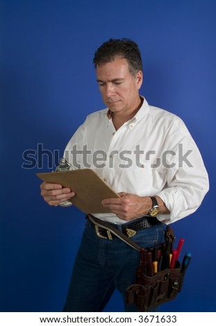 A man with a toolbelt around this waist looking at something on a clipboard. - stock photo