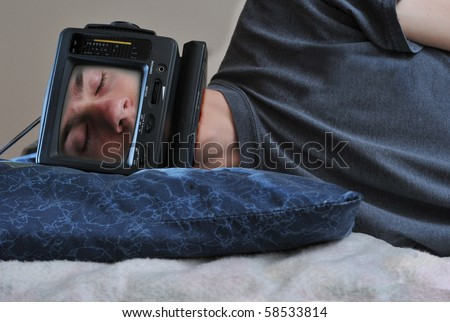 A man with a TV on his head sleeping on his bed, off. - stock photo