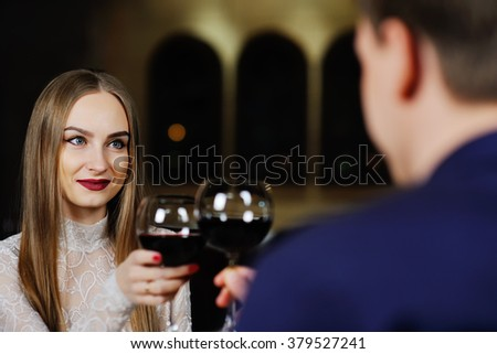 a man with a woman drinking red wine in a restaurant