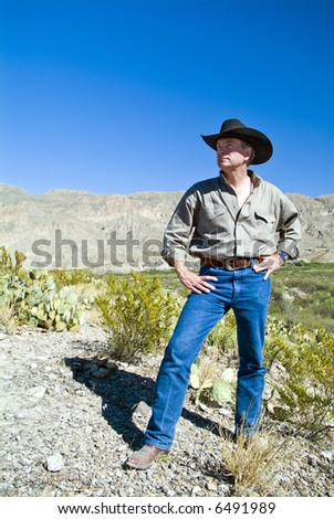 A man with an appreciative expression on his face, surveying the rugged beauty surrounding him. - stock photo