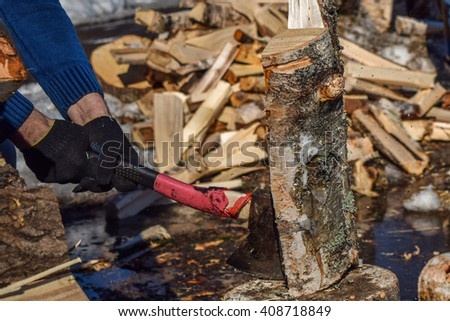 a man with an ax chopping wood outdoors closeup