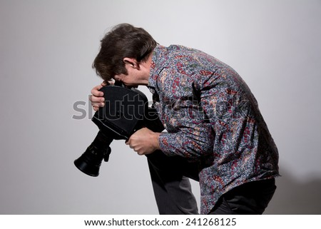 A man with an old movie camera on a gray background. Videographer to capture directs the camera down - stock photo