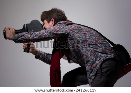 A man with an old movie camera on a gray background. Videographer to capture directs the camera to the side - stock photo