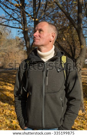 A man with backpack enjoying life, relaxing in a autumn park, he looks up, admiring  the blue sky, standing on the background of colorful autumn leaves. Sunny day by autumn.