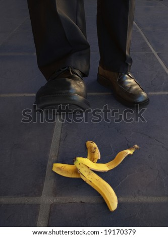 A man with black shoes about to step on a banana peel.