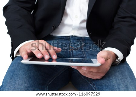 A Man with blue jeans working on a tablet pc with he's hand - stock photo