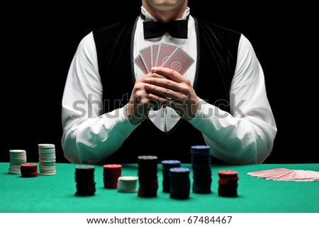 A man with bow tie playing poker - stock photo