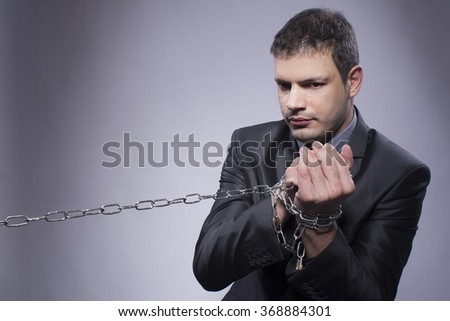 A man with chains standing showing his hands. Studio shot.
