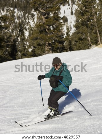 A man with chest pack skiing downhill at lake Tahoe resort, Sierra Nevada, California.