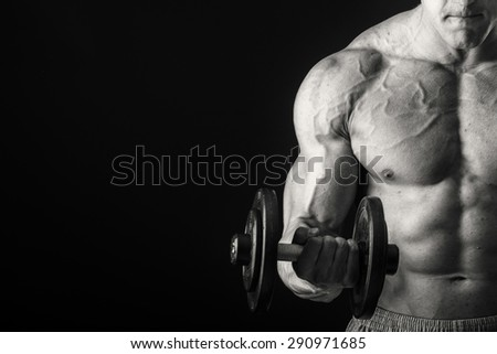 A man with dumbbells on black - stock photo