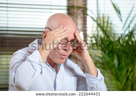 a man with glasses who has a headache - stock photo