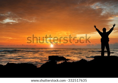 a man with hands raised to beautiful Silhouette  sunset  - stock photo