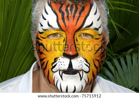 A man with his face painted as a tiger with tropical leaves in the background. - stock photo