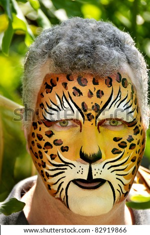 A man with his face painted like a leopard. - stock photo