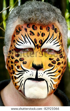 A man with his face painted like a leopard looking mean. - stock photo