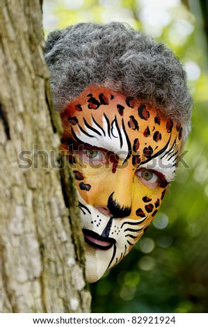 A man with his face painted like a leopard peeking around a tree. - stock photo