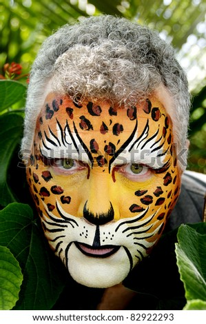 A man with his face painted like a leopard peeking out of large leaves.