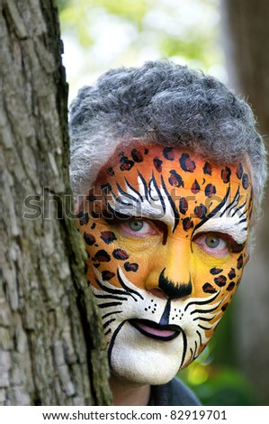 A man with his face painted looking out from behind a tree. - stock photo