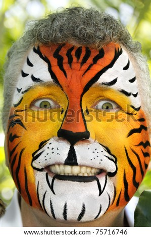 A man with his face painted to appear like a tiger, looking frightened. - stock photo
