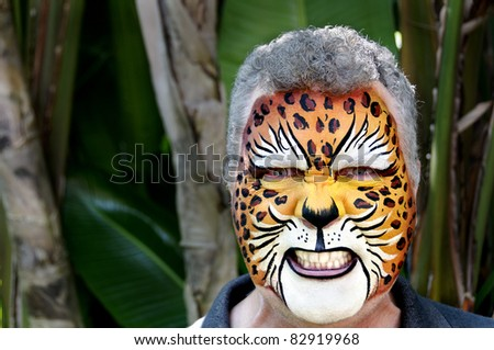 A man with his face painted to look like a leopard, growling. - stock photo