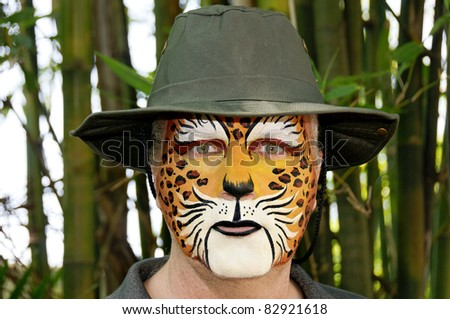 A man with his face painted to look like a leopard wearing a hat. - stock photo
