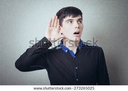 A man with his hand near his ear. Gesture can not hear without listening, talking louder. On a gray background - stock photo