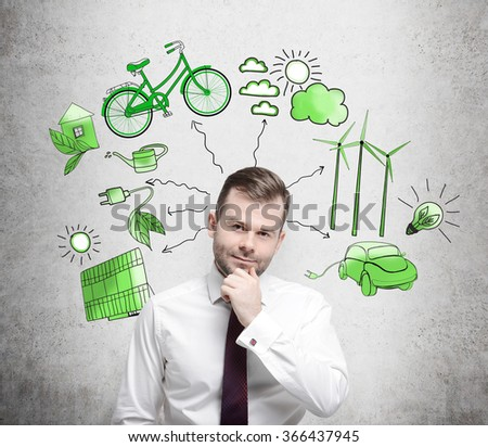 A man with his hand to the chin thinking, symbols of alternative energy sources painted in green colours on a white poster behind him. Concept of clean environment. - stock photo