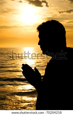 A man with his hands folded in prayer in front of a golden sea.