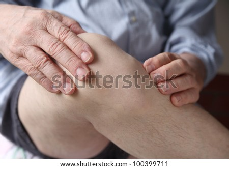 a man with his hands on a painful knee joint - stock photo
