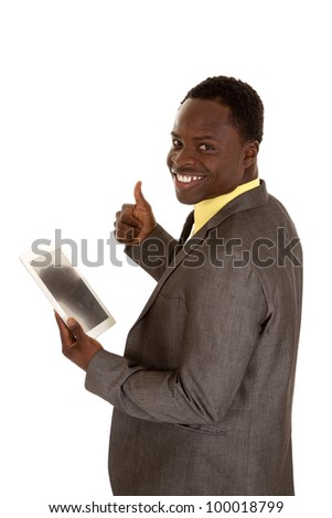A man with his thumb up with a smile on his face holding on to his tablet. - stock photo