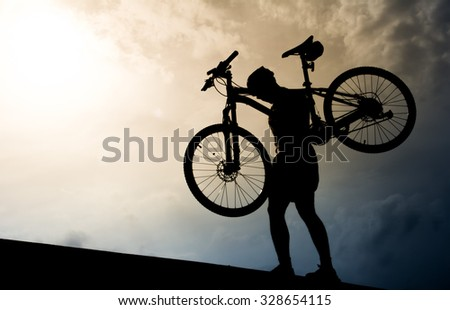 A man with mountain bicycle lifted above him. Silhouette style. - stock photo