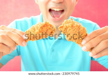 A man with opening mouth about to eat deep fried chicken legs or drumsticks - stock photo