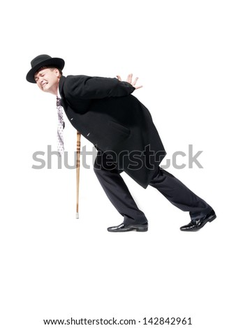 A man with pain walks with the assistance of a cane. - stock photo