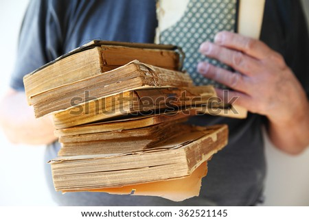 A man with several vintage, well-used books in his hands - stock photo