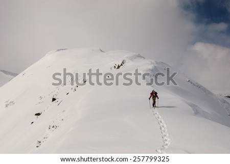 A man with snowshoes walking on a snow mountain ridge. - stock photo