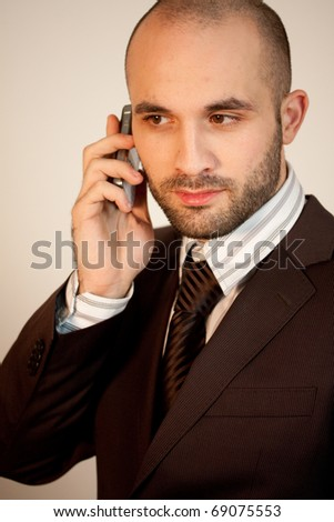 A man with suit uses a phone
