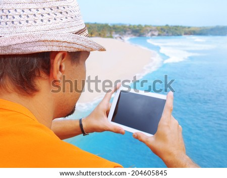 a man with tablet in hand on the beach - stock photo
