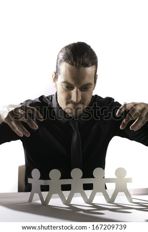 A man with tattoos looks intensley at the camera.  He is holding a large knife and stares wide eyed through dishevelled hair. - stock photo