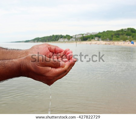 A man with water in his hands with shallow depth of field and copy space.