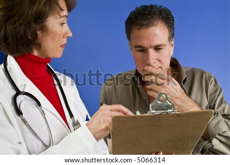 A man with what appears to be a doctor looking over something on a clipboard. - stock photo